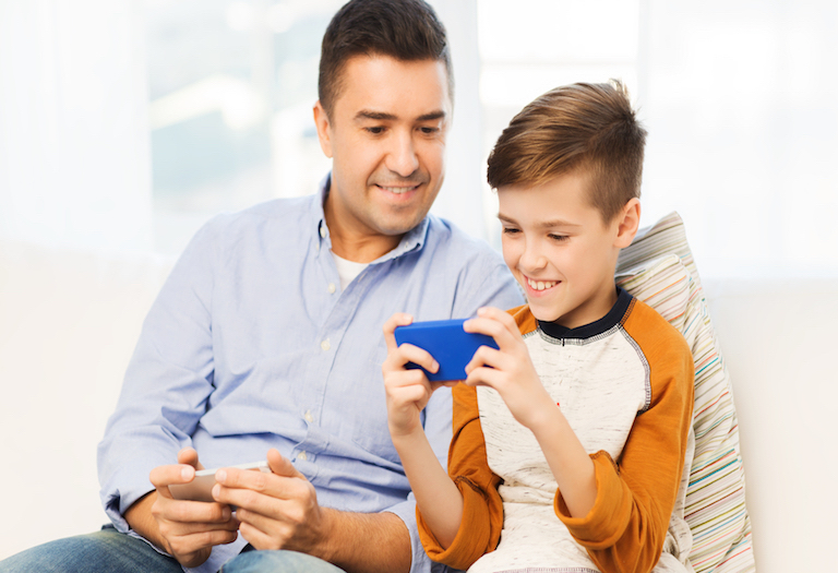 happy father and son with smartphone at home